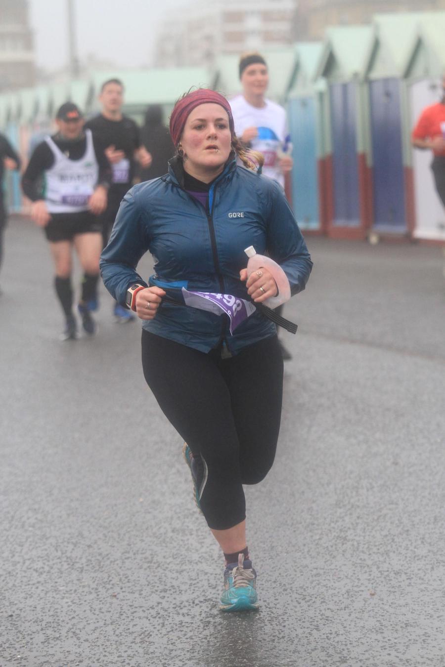 Runner running past beach huts during 2020 Brighton Half Marathon